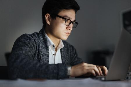 Foto de Asian Man Working with Laptop at Night - Imagen libre de derechos