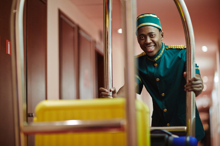 Photo pour Smiling Bellboy Carrying Luggage in Cart - image libre de droit