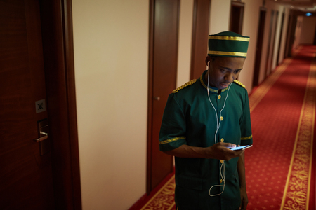 Photo pour Bellboy Listening to Music in Hotel Hall - image libre de droit