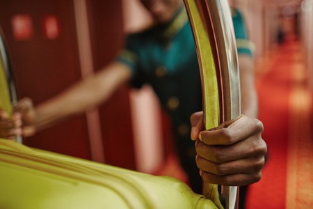 Photo pour Closeup portrait of African-American bellhop pushing luggage cart delivering bags to hotel rooms in hallway, helping guests - image libre de droit