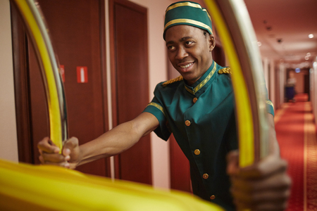 Photo pour Bellboy Delivering Bags in Hotel - image libre de droit