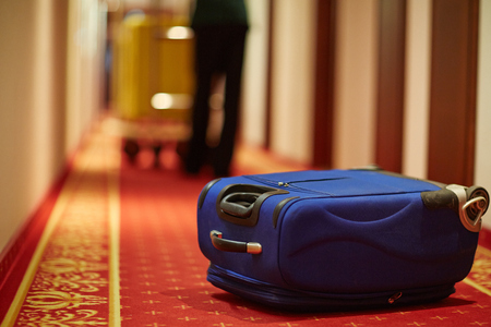Photo pour Closeup shot of bellboy carrying luggage in hotel hallway, focus on blue suitcase on floor by room door - image libre de droit