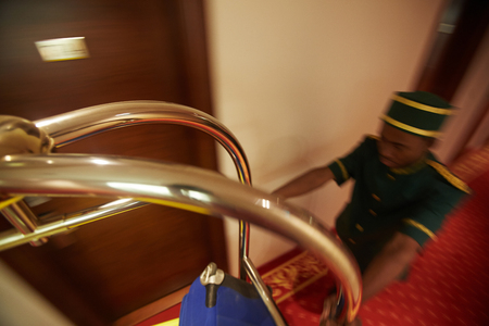 Photo pour Fast Bellboy Pushing Luggage Cart in Hotel Hall - image libre de droit