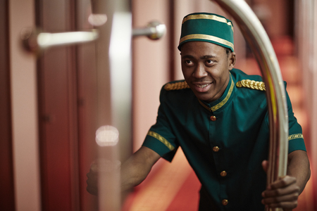 Photo pour Smiling Bellboy Pushing Luggage Cart in Hotel Hallway - image libre de droit