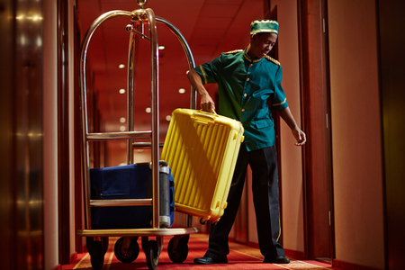 Photo pour African Bellboy Delivering Luggage to Hotel Rooms - image libre de droit