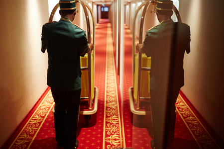 Photo pour Bellboy Pushing Luggage Cart in Hotel Hallway - image libre de droit