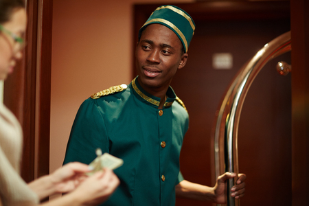 Photo pour Bellboy Getting Tips from Guests - image libre de droit
