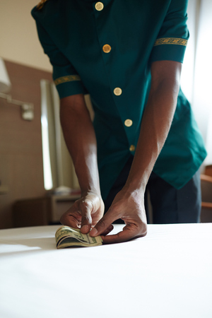 Photo pour Closeup shot of unrecognizable African bellhop taking cash money from table in hotel room - image libre de droit