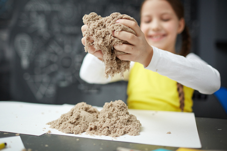 Photo pour Happy Little Girl Playing with Kinetic Sand at Daycare Center - image libre de droit
