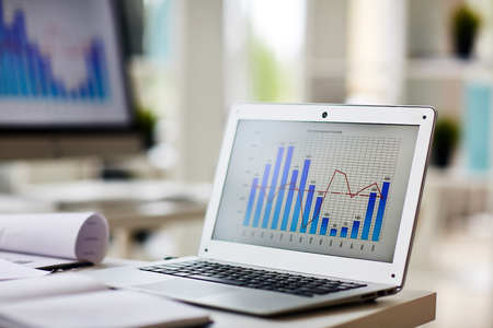 Foto de Laptop with chart on its display at workplace of economist - Imagen libre de derechos