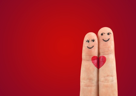Photo for A happy couple in love with painted smiley and hugging - Royalty Free Image