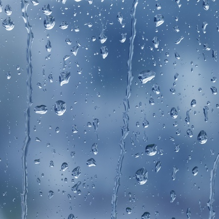 abstract full frame background showing a window with raindrops rolling off (blue toned)