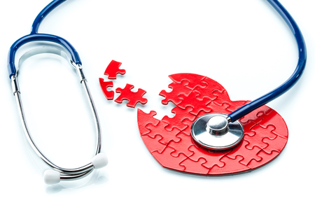 Foto de Heart disease, puzzle heart with stethoscope on white background - Imagen libre de derechos