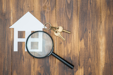Foto de paper house and key with Magnifying Glass, House hunting on wooden background - Imagen libre de derechos