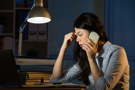 Photo for asian business woman headache on smartphone working overtime late night. indoors office background - Royalty Free Image