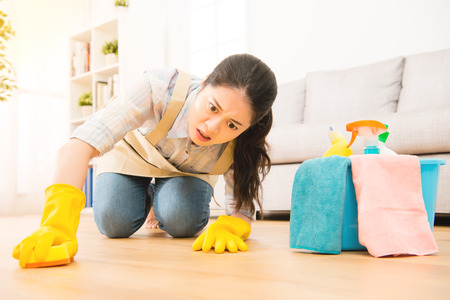 Photo for housewife scrub hardly cleaning floor in protective gloves with struggle face expression kneeling on wooden ground at home. mixed race asian chinese model. - Royalty Free Image