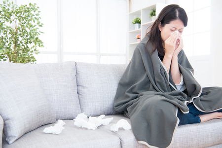 Photo for Sick young woman sneeze at home on the sofa with a cold, she is covering with a blanket and blowing her nose. medical and health concept. mixed race asian chinese model - Royalty Free Image