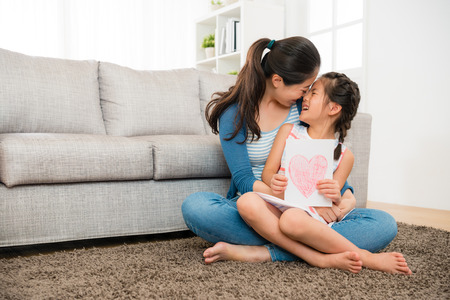 Photo pour happy mom holding happy little daughter and giving her kiss sitting on the living room floor when she knowing girl prepare mother's day card gift. - image libre de droit