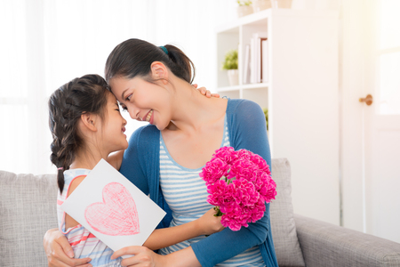 Foto de young asian mother accept the little daughter hand painted card embrace holding a pink flower girl sitting on the sofa in the living room happy looking at each other with copy space at mother's day. - Imagen libre de derechos