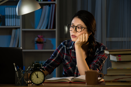 Photo pour Studies late at night staying up late. Young exhausted concentrated student feel sleepy at the desk in her room in the dark at the lamp. mixed race asian chinese model. - image libre de droit