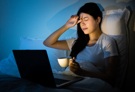 Photo pour businesswoman rubbing eyes drinking coffee to working with computer sitting on bed at room. mixed race asian chinese model. - image libre de droit