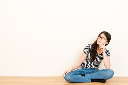 Photo pour mixed race asian woman thinking question feel confusion. wearing t-shirt top sitting on wooden floor over blank copy space white wall background. - image libre de droit