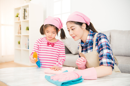Foto de young asian woman and a little child girl wiped the dusting table in the living room at home. Mother and daughter do the cleaning in the house. family housework and household concept. - Imagen libre de derechos