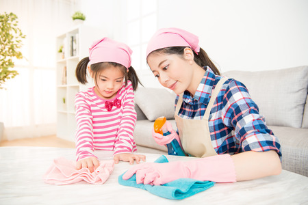 Foto de asian chinese mother and kids cleaning room together. happy family do the dusting at home. housework and household concept. - Imagen libre de derechos
