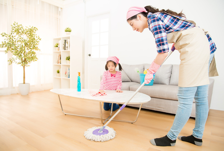 Foto de mum teaching daughter cleaning their home living room at weekend. A young woman and a little child girl dusting. family housework and household concept. - Imagen libre de derechos