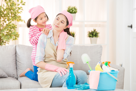 Foto de housewife feel tired and neck painful after doing the house cleaning at home, her daughter help her massage release muscle pain. housework and household concept. - Imagen libre de derechos