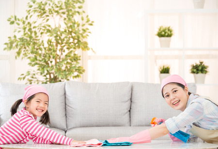 Photo pour Young happy mother and her little daughter cute girl, cleaning the house together sweeping the table in a white sunny living room with modern interior. family housework and household concept. - image libre de droit