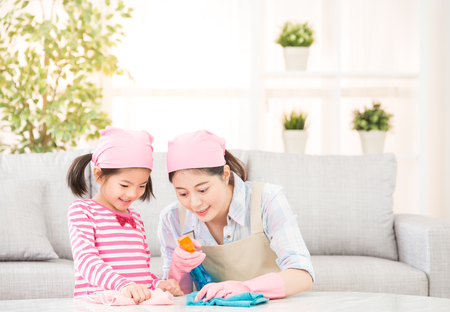 Foto de Happy family cleans the living room. Mother and daughter do the cleaning in the house. A young woman and a little child girl dusting. family housework and household concept. - Imagen libre de derechos