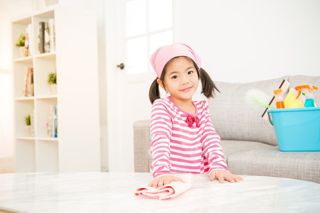 Foto de asian chinese cute little girl help make cleaning in the living room at home. housework and household concept. - Imagen libre de derechos