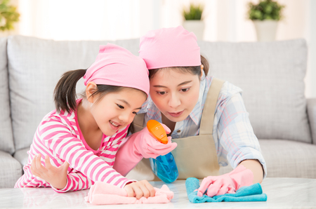 Foto de mixed race Asian Chinese mother and daughter do the cleaning in the house. Happy family cleans the room. A young woman and a little child girl dusting. family housework and household concept. - Imagen libre de derechos