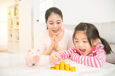 Foto für little asian chinese girl kids excited to see how much money she has deposit in her piggy bank with her mother in the living room at home. family activity concept. - Lizenzfreies Bild