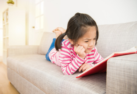 Foto de happy little asian chinese girl lying down on sofa reading story book feel hard and difficult to understand the content in the living room at home. family activity concept. - Imagen libre de derechos
