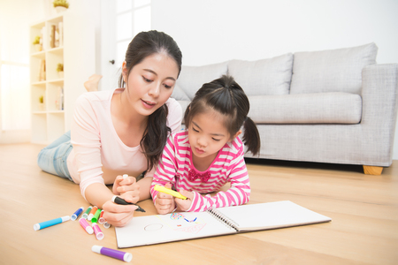 Foto de Mother and daughter are lying down on wooden floor having fun while drawing in the living room at home. family activity concept. - Imagen libre de derechos