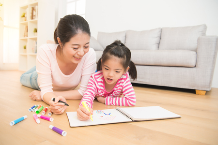 Foto de Happy mixed race asian mother and daughter together paint. adult woman helps the child girl lying down on wooden floor drawing sketchbook in the living room at home. family activity concept. - Imagen libre de derechos