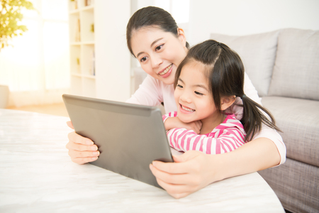 Foto de Beautiful asian chinese young woman and her charming little daughter are using a digital tablet and smiling while in the living room at home. family activity concept. - Imagen libre de derechos