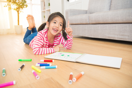 Foto de Children kids dreaming got some new idea lying down on wooden floor near sketchbooks and drawing in the living room at home. family activity concept. - Imagen libre de derechos