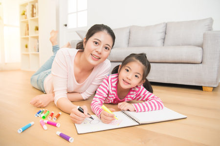 Photo for happy asian little girl painting drawing with her mother lying down on wooden floor drawing sketchbook in the living room at home. family activity concept. - Royalty Free Image