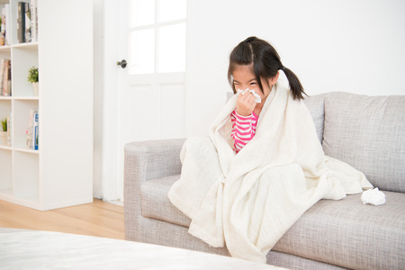 Foto de Little girl sick  blowing her nose with tissue and cover with blanket sitting on sofa in the living room at home. family activity concept. - Imagen libre de derechos