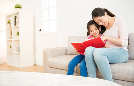 Photo pour happy asian chinese mother and little daughter girl reading a book in the morning together in the living room at home. family activity concept. - image libre de droit