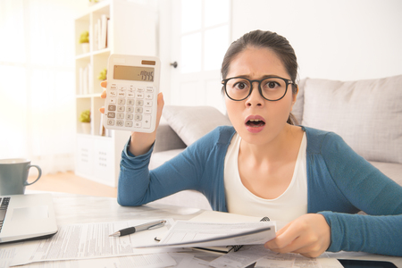 Foto de Shocked woman counting expensive electricity and household bills feel shocked after see the numbers sitting on sofa in the living room at home. interior and domestic housework concept. - Imagen libre de derechos