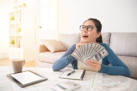 Photo pour Closeup portrait happy excited successful young student girl holding money dollar bills in hand looking up dreaming. Positive emotion facial expression feeling. Financial reward - image libre de droit