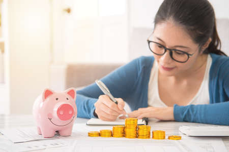 Photo pour piggy bank money tower in front of happy asian chinese house woman counting and recording her savings sitting on sofa in the living room at home. indoors interior and domestic housework. - image libre de droit