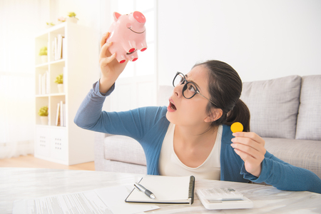Foto de young unhappy woman emptying her piggybank savings with less than expected sitting on sofa in the living room at home. interior and domestic housework concept. - Imagen libre de derechos