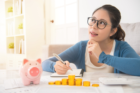 Photo pour happy asian chinese house woman dreaming and recording writing her savings from piggy bank money tower sitting on sofa in the living room at home. indoors interior and domestic housework. - image libre de droit