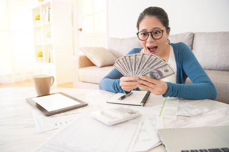Photo pour portrait of happy excited successful young business woman holding money dollar bills and looking at cash feel surprised sitting at living room. Positive emotion facial expression feeling. - image libre de droit