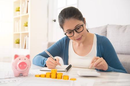 Foto de smile mixed race asian chinese house woman counting her savings from piggy bank money tower sitting on sofa in the living room at home. indoors interior and domestic housework. - Imagen libre de derechos
